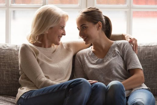 Une femme mature et sa fille souriante discute de l'assurance vie et succession