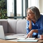 Une dame âgée se documente sur internet à propos des avantages de l'assurance vie et des reer